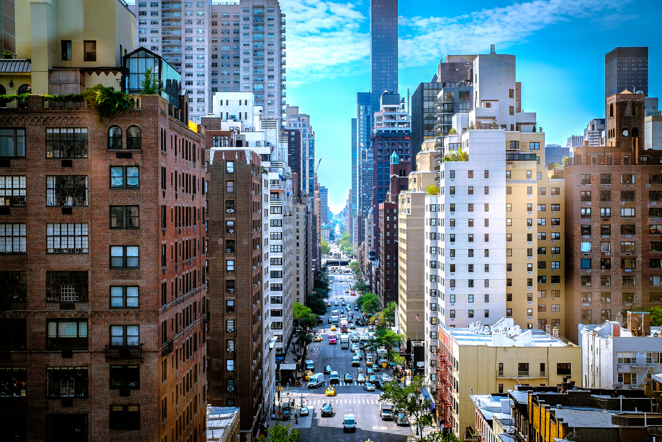 A colorful street canyon in New York City. The blue sky along with some clouds build a nice background for the busy street.